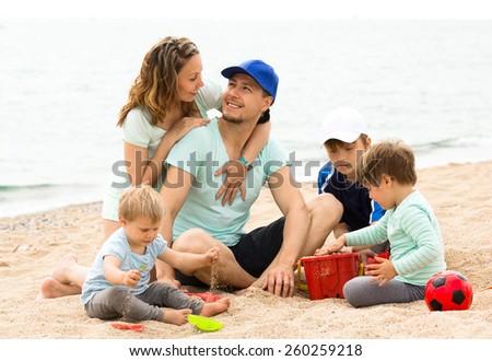 parents with children enjoying rest on  beach - stock photo