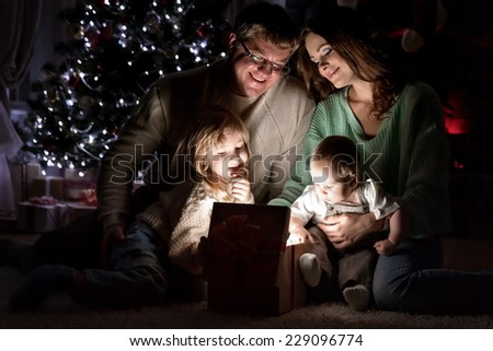 Parents with children is considered a magical gift on Christmas Eve under the Christmas tree by the fireplace - stock photo