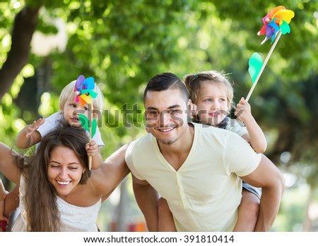 Parents with children playing colorful windmills in park on sunny day - stock photo