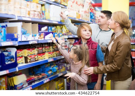 Parents with children standing in supermarket and choosing cereal for breakfast . Selective focus