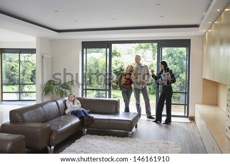 Parents with daughter and female estate agent observing new property - stock photo