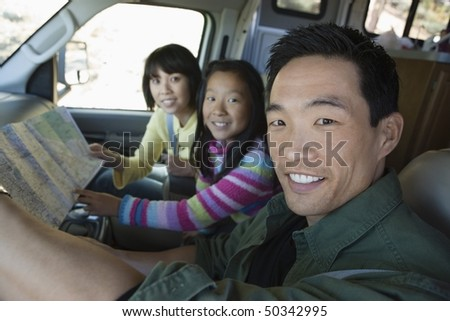 Parents with daughter looking at map in RV - stock photo
