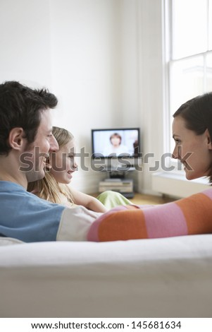 Parents with daughter relaxing on sofa in living room - stock photo