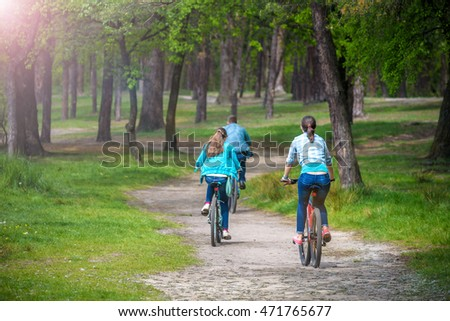 Parents With Daughter Riding Bikes In Park or summer forest. View from back, selective focus.