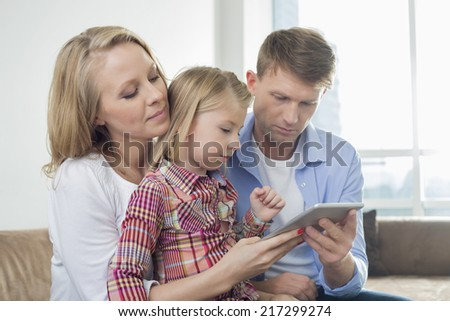 Parents with daughter using digital tablet at home - stock photo