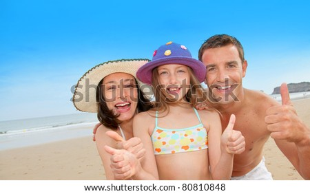 Parents with girl showing thumbs up - stock photo