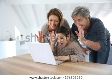 Parents with kids making a distant call on internet - stock photo