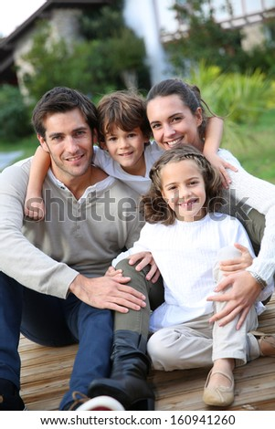 Parents with kids relaxing in front of home - stock photo