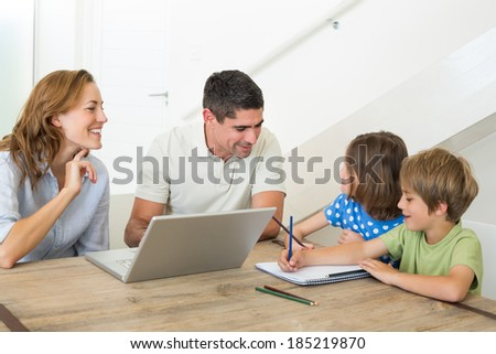 Parents with laptop assisting children coloring at table in house