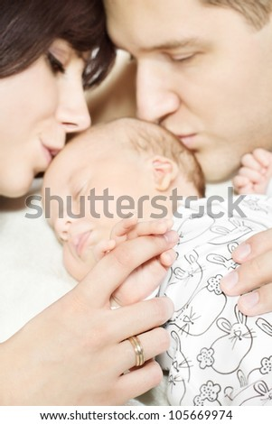 Parents with newborn baby lying down and kissing child. Family and parenting concept - stock photo