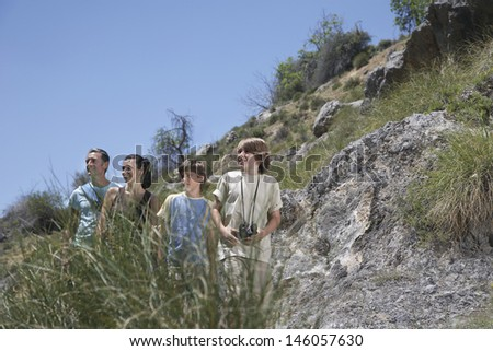 Parents with smiling two sons in mountains looking at view against clear blue sky - stock photo