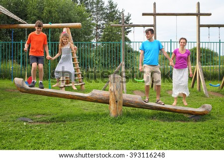 Parents with son and daughter happy jumping on a swing on a wooden playground - stock photo