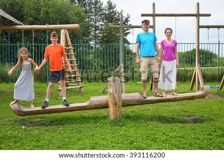 Parents with son and daughter swinging on a swing on a wooden playground - stock photo