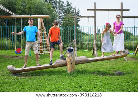 Parents with son and daughter teetering on a swing on a wooden playground - stock photo