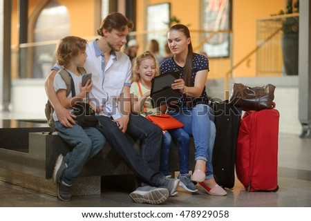 Parents with two children at the railway station. Family in large waiting room. All have settled down on bench. Mom shows something interesting on the screen of the tablet. Nearby are the travel bags.