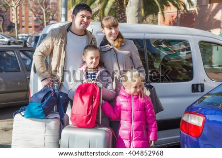 Parents with two daughters with suitcases in journey