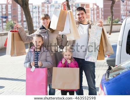 Parents with two girls holding shopping bags in sunny day