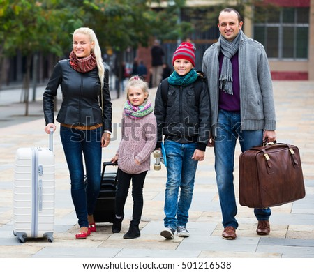 Parents with two kids and baggage chasing streets in barcelona