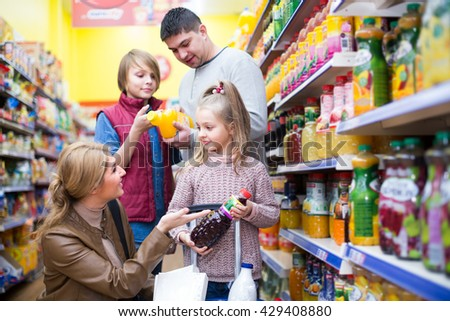Parents with two kids choosing russian soda and juice in shop