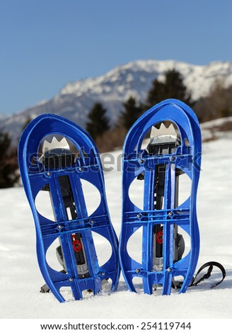 pari of orange modern snowshoes in the mountain - stock photo
