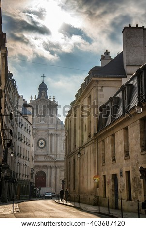 Paris alley way with a church at the end under a cloudy day - stock photo