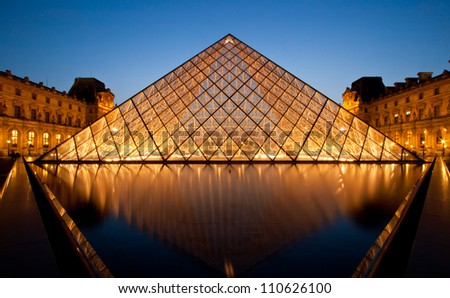 PARIS-APRIL 16: Louvre pyramid shines at dusk during the Summer Exhibition April 16, 2010 in Paris. Louvre is the biggest Museum in Paris displayed over 60,000 square meters of exhibition space. - stock photo