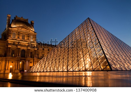 PARIS - APRIL 25: Louvre Pyramid shines at dusk on April 25, 2013 in Paris. Louvre is the biggest Museum in Paris displayed over 60,000 square meters of exhibition space. - stock photo