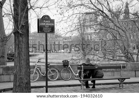 PARIS - APRIL 18: Romantic couple on parisian embankment on April 18, 2013 in Paris, France. Paris is one the most popular romantic city in the world. - stock photo