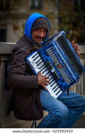 PARIS - APRIL 28, 2016: Sidewalk accordion player in Paris. - stock photo