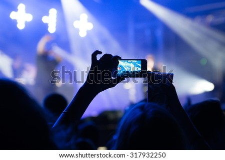 PARIS - AUG 31: A man takes a picture with his smartphone in a concert at Rock En Seine Festival on August 31, 2015 in Paris, France. - stock photo