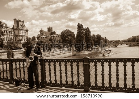 PARIS - Aug 14: Unidentified young saxophone player on the bridge as seen on August 14, 2013 in Paris, France. Dozens buskers perform on the streets and in the metro of Paris. - stock photo