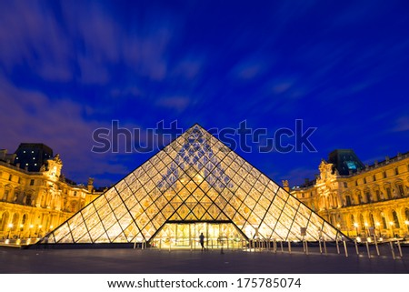 PARIS - AUGUST 05: A person stands in front of the Louvre Pyramid at night on August 05, 2010 in Paris, France. The Louvre is one of the major tourist attractions in France and Europe. - stock photo