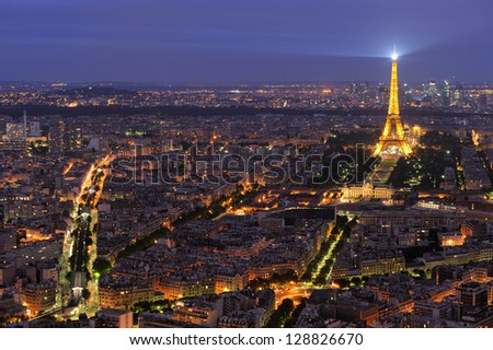 PARIS - AUGUST 11: Aerial view of Paris by night. Illuminated Eiffel tower and colorful streets. August 11, 2009. - stock photo