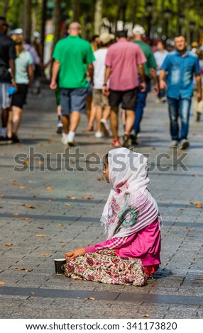 PARIS - AUGUST 10:  An unidentified female begs on the street in the Champs-Elysees on August 10, 2015 in Paris, France. The number of beggars is considerably higher due to the current economics - stock photo