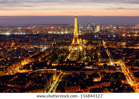 PARIS -  6  AUGUST  2013: Illuminated Eiffel Tower at night and people on the Champs de Mars. The popular place for people for romantic evenings