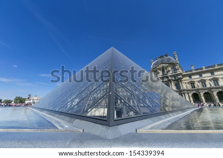 PARIS - AUGUST 11: Louvre pyramid during the Summer Exhibition on August 11,2013 in Paris.Louvre is the biggest Museum in Paris displayed over 60,000 square meters of exhibition space. - stock photo
