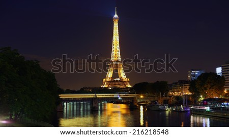 PARIS - AUGUST 29: The illuminated Eiffel Tower and bridge Pont de Bir-Hakeim on Aug 29, 2014 in Paris, France.The Eiffel tower is most visited monument of France with 6 million visitors every year - stock photo