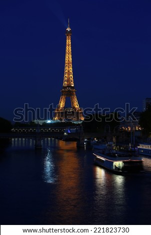 PARIS - AUGUST 27: The illuminated Eiffel Tower and bridge Pont de Bir-Hakeim on Aug 27, 2014 in Paris, France.The Eiffel tower is most visited monument of France with 6 million visitors every year - stock photo