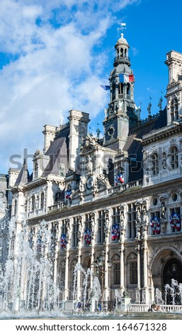 Paris City Hall (Hotel de Ville) decorated with flags and fountains in sunny day. - stock photo