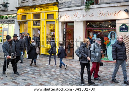 PARIS - Dec 23, 2013: Historic Jewish quarter. Pedestrian street Rue des Rosiers, a picturesque area of small shops and bakeries visited by locals and tourists. - stock photo