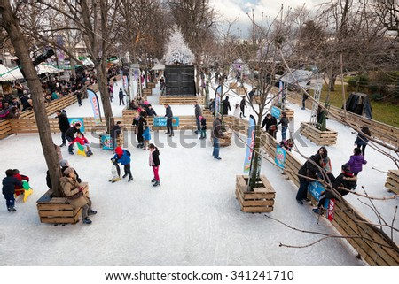 PARIS-Dec 25, 2013: Ice skating at the Christmas Market and Santa's Village on Avenue des Champs-Elysees, a popular holiday tradition for Parisian children and families. Image taken on Christmas Day. - stock photo