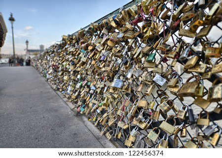 PARIS - DEC 1: Locks at Pont des Arts symbolize love for ever, December 1, 2012 in Paris. 16000 lockers of loving couples are on that bridge, also known as Passarelle des Arts - stock photo
