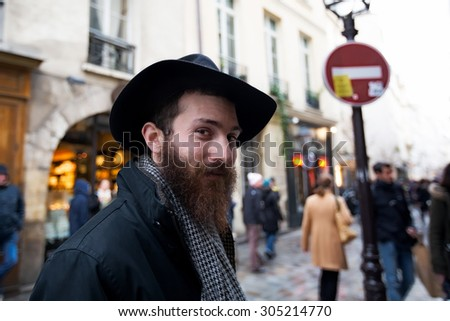 PARIS-DEC 31, 2013: Rue des Rosiers in the Jewish district of the historic Le Marais neighborhood. An unidentified man in the foreground wears a type of black hat worn by orthodox Jews. - stock photo