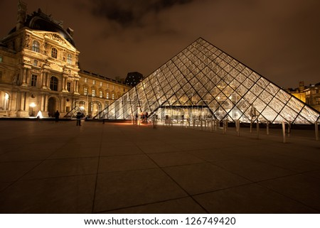 PARIS - DEC. 3: The Louvre Art Museum on December 3, 2010 in Paris. The history of this most famous museum goes back 800 years of continuous transformations from fortress to palace and museum. - stock photo