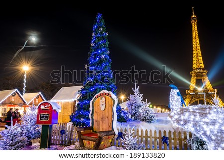 PARIS - DECEMBER 16, 2013: A Christmas tree in the Trocadero gardens. The Eiffel Tower in the background projects the colors of the South African flag as a tribute to Nelson Mandela. - stock photo