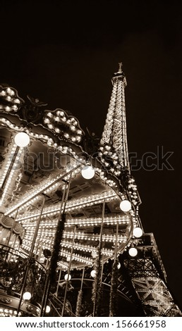 PARIS - DECEMBER 29: Eiffel Tower and antique carousel as seen at night on December 29, 2012 in Paris, France. The Eiffel tower is the most visited paid monument in the world. - stock photo