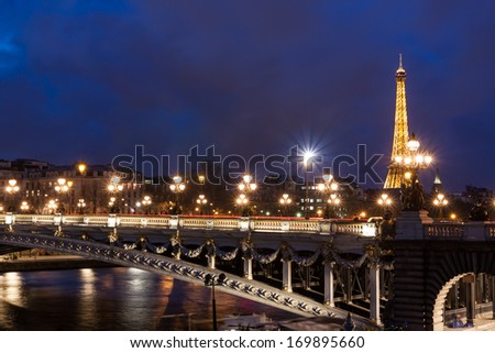 PARIS - DECEMBER 25: Eiffel Tower and Pont Alexandre III at night on December 25, 2013 in Paris. Paris is one of the most visited cities in the world with about 28 million of visitors every year. - stock photo