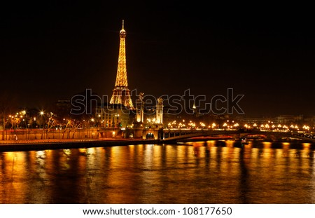 PARIS- DECEMBER 11:Night image of the Seine river and the Eiffel Tower 0n December 11 2011 in Paris,France..Eiffel Tower is the most popular French touristic attraction. - stock photo