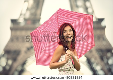 Paris Eiffel Tower Woman happy smiling in front of tourist attraction Eiffel Tower. Joyful fresh Caucasian Asian girl laughing. - stock photo