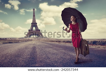 Paris. Eiffel tower. Young business woman hurrying up with luggage and umbrella on highway. Business trip to France concept.  - stock photo